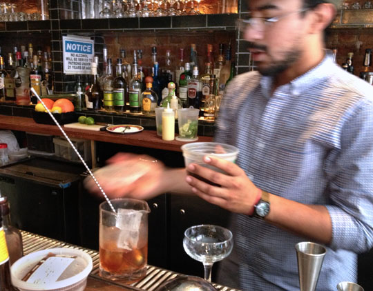 Wilmer Nolasco, a server and bartender at 'Cue in the West Village, makes a fat-washed Rye Manhattan.  Photo by Donna Turner Ruhlman.